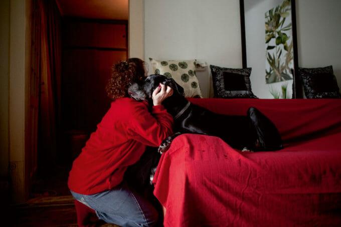 femeie care își îmbrățișează câinele ce stă pe o canapea acoperită cu o pătură roșie