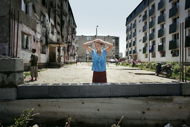 O fata se uită în cameră din spatele unui zid.