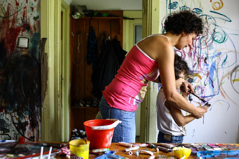 O mama si fiul ei cu autism picteaza pe un perete.