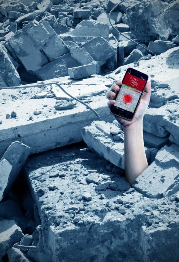 o mână străpunge betonul ținând un smartphone în mână care afișează o alarmă