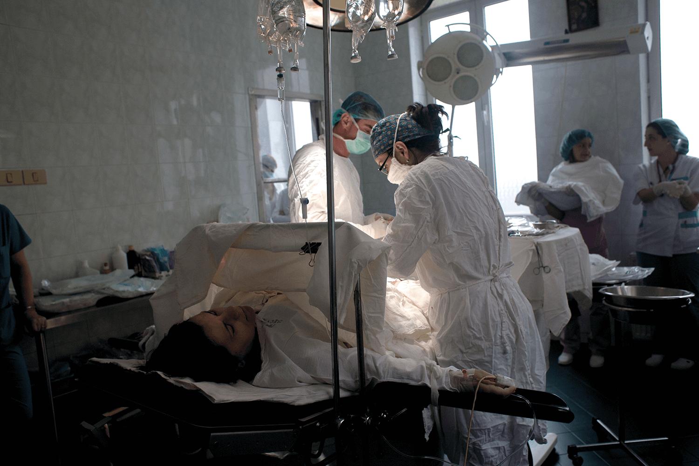 femeie în sala de operație, în timpul unei intervenții de cezariană