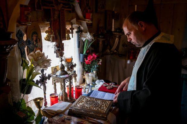 preot în altar, citind de pe o hârtie