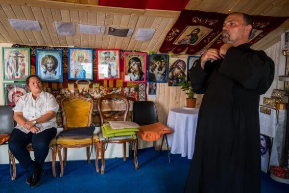 preot și credincioasă, în interiorul unei biserici placate cu pal și scânduri