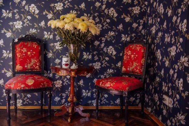 colț din biroul Anei Morodan - 2 scaune roșii tapițate, un buchet de crizanteme pe o masă de lemn și tapet floral.