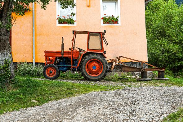 tractor oprit în fața unei sate țărănești.