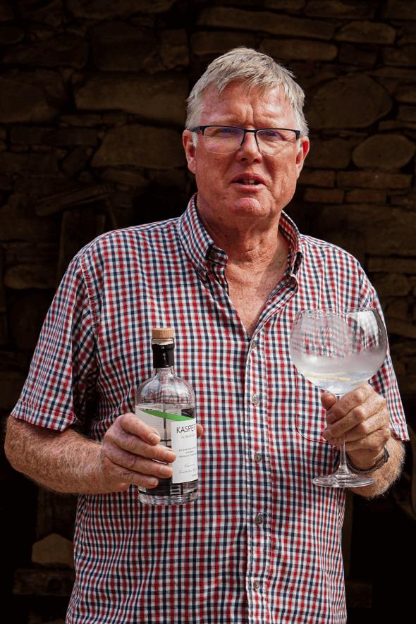 portret Jim Turnbull ținând în mână un pahar de gin din soc.
