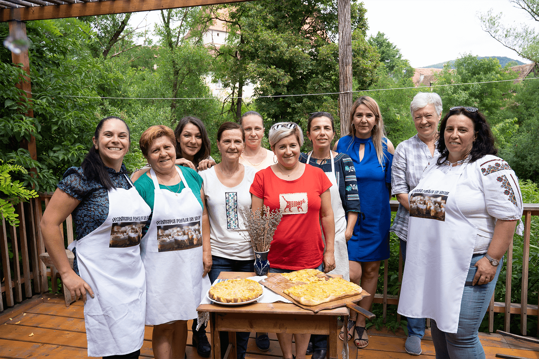 femei cu șorț, în jurul unei mese pe care vedem o plăcintă și pizza cu rubarbă așezată pe un tocător.