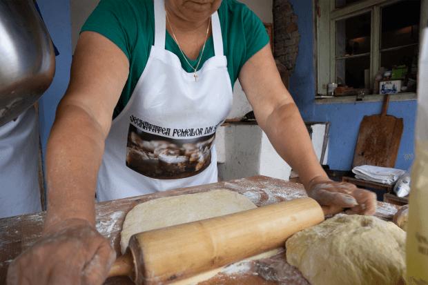 Femeie întinde cu făcălețul aluat pentru pizza și pâine