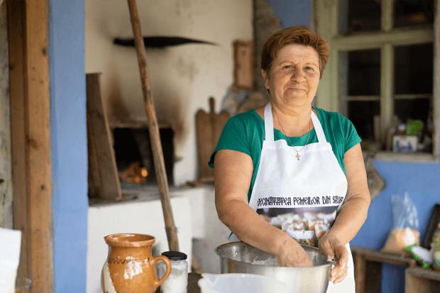 portret femeie cu șorț în bucătărie tradițională, în timp ce frământă aluatul