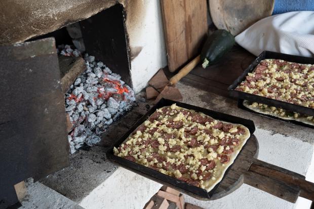 pizza cu rubarbă este așezată pe un fund de lemn, urmând să intre în  cuptorul încins cu lemne