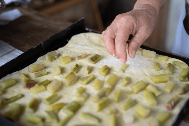 mâna care așază bucățile de rubarbă pe aluat