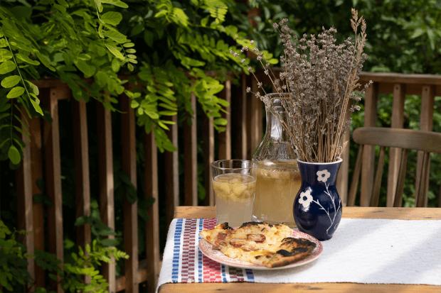 masă de lemn pe care stă o vază bleumarin cu flori de lavandă, pahar și carafă de limonadă, o felie de pizza cu rubarbă