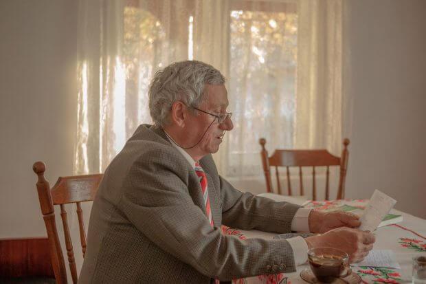 bărbat surprins din profil stă la masă și citește