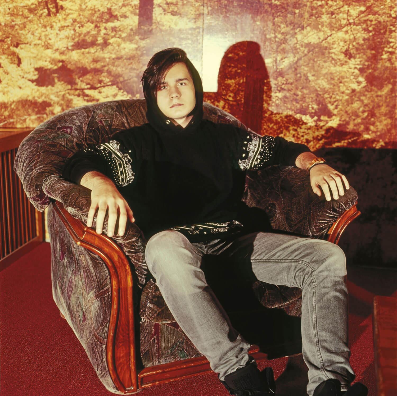 Cosmin Ghibănescu stă pe un fotoliu, într-o cameră cu tapet ce imită copacii înfrunziți.