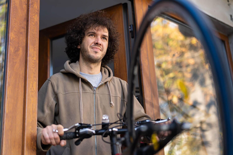 un bărbat ține în mână o bicicletă privind înainte