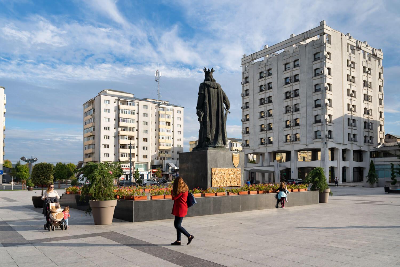 oameni, statuia lui Ștefan cel Mare și ghivece de flori în centrul orașului Vaslui