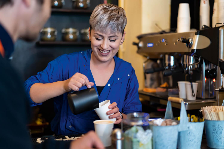 o femeie blondă, tunsă scurt, pregătește o cafea cu lapte într-o cafenea