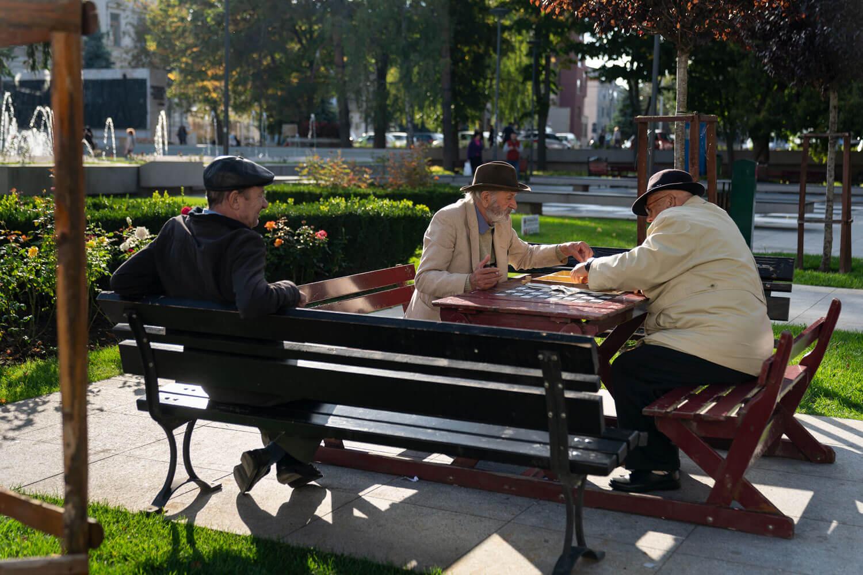 trei pensionari joacă șah pe băncile unui parc din Vaslui.