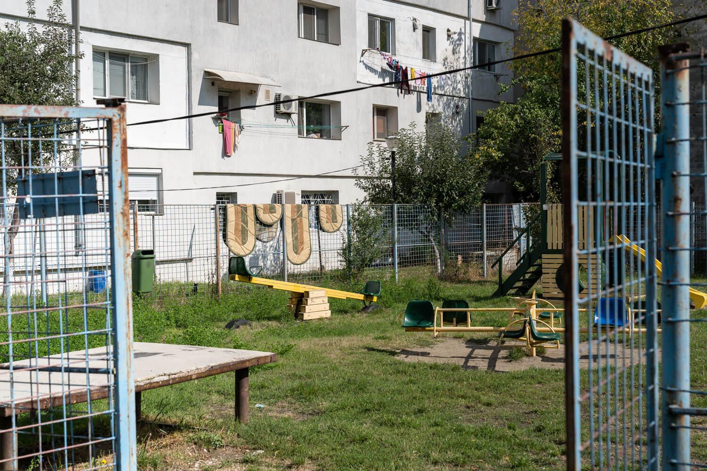 covoare puse la uscat într-un loc de joacă construit în spatele blocurilor