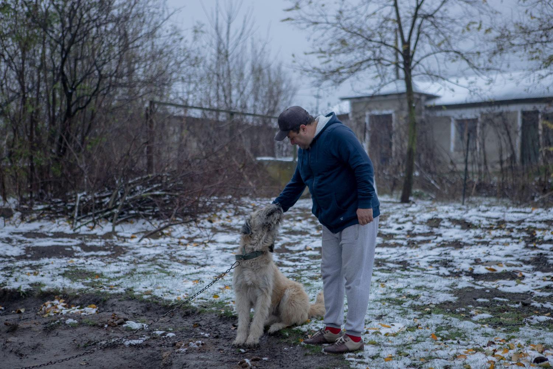 un bărbat își mângăie câinele în curtea sa iarna