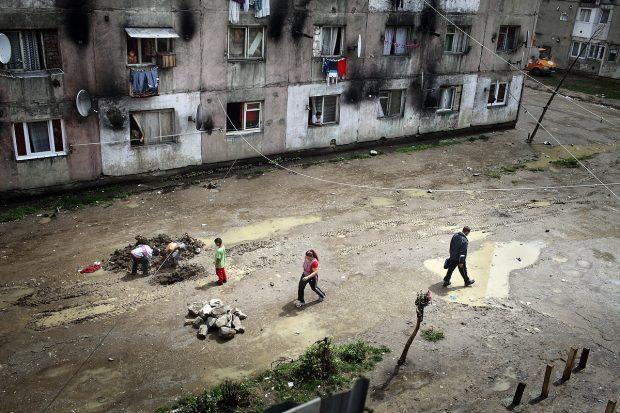 Oameni merg prin băltoace între blocuri.