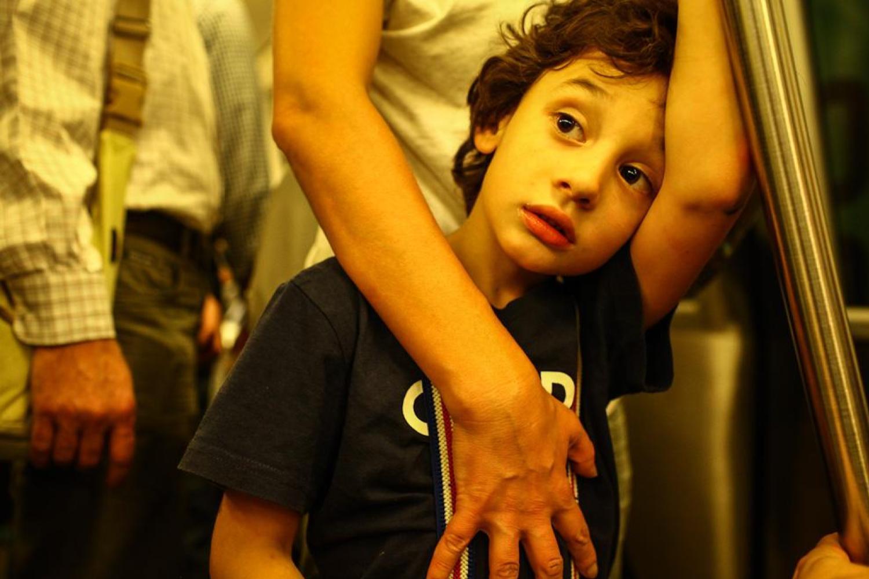 un copil cu părul ondulat se uita in zare.