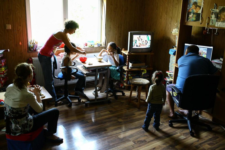 Mai multi copii si parintii lor stau impreuna si mananca la centrul de terapie.