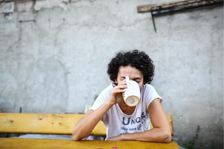 Mirela bea cafeaua de pe o banca.