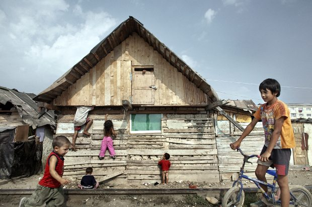 Copii se urcă pe o casă din lemn.