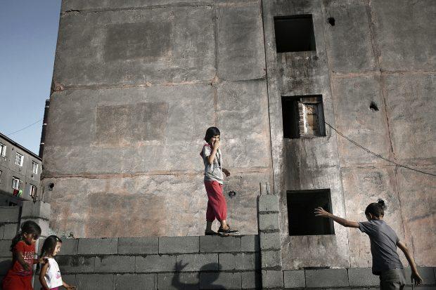 Un copil se joacă pe zid.