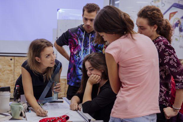 O femeie explică ceva unui grup de elevi, în jurul unor hârtii.