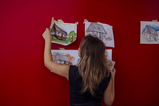 O femeie lipește niște hârtii cu picturi pe un perete.