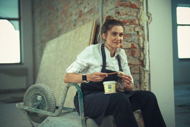 O femeie bucatar sta pe un santier in ceea ce va fi restaurantul ei.