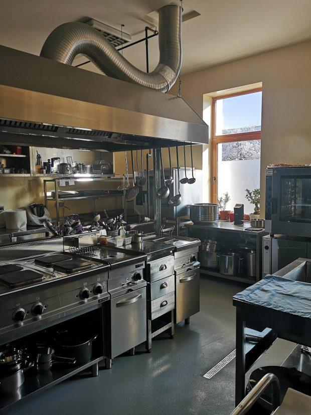 O bucatarie de restaurant intr-o lumina calda de la soarele care intra prin ferestrele mari.