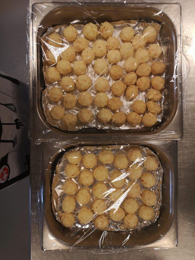 Chiftele din brânză așezate în două tăvi și acoperite cu o folie de plastic.