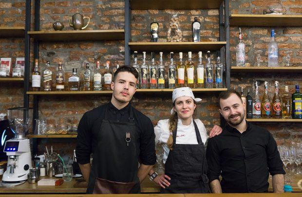 Barmanii și Mădălina Santa, cheful restaurantului, în fața barului.