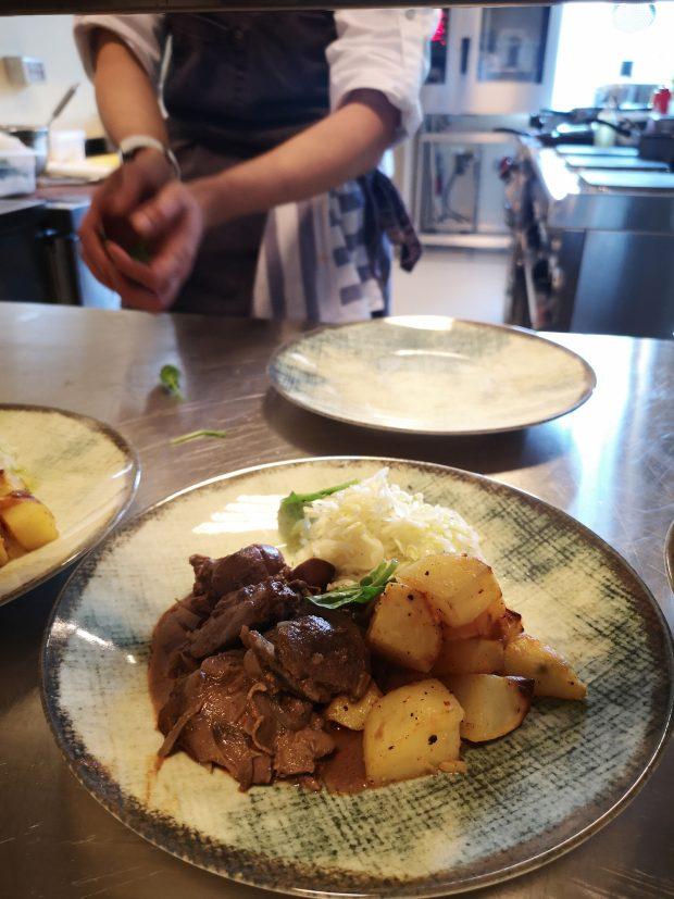 O farfurie cu ficatei de pui si ceapa, cartofi la cuptor si salata de varza.