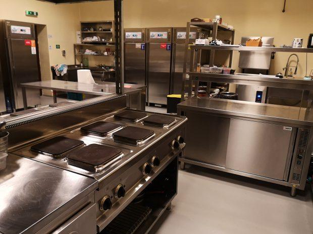 O bucătărie cu multe blaturi din inox curățate foarte bine la final de zi.