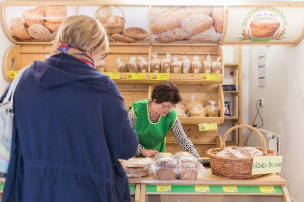 O femeie caută un produs de panificație pentru o altă femeie care vrea să îl cumpere.