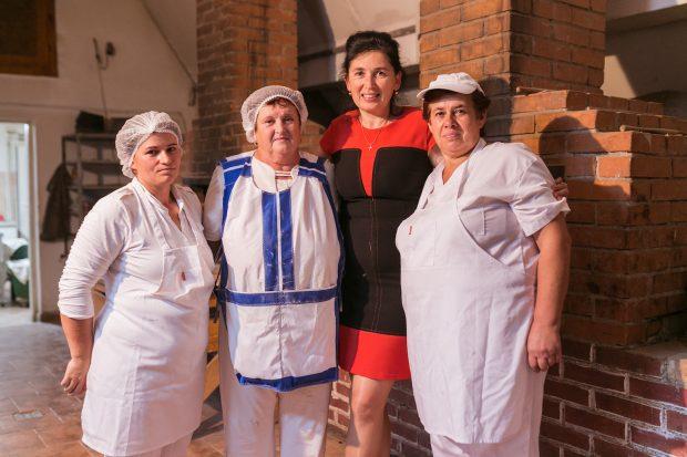 Patru femei zâmbesc în fața camerei într-o brutărie.