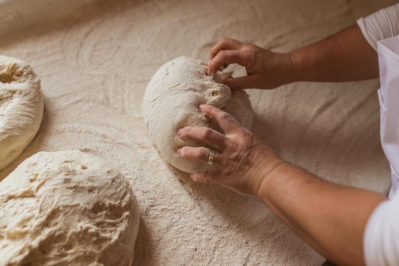 O femeie frământă pâine pe o masă.