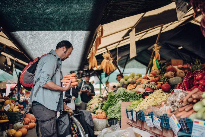 Ioan Bebeșelea în piață, ține niște morcovi în mână.