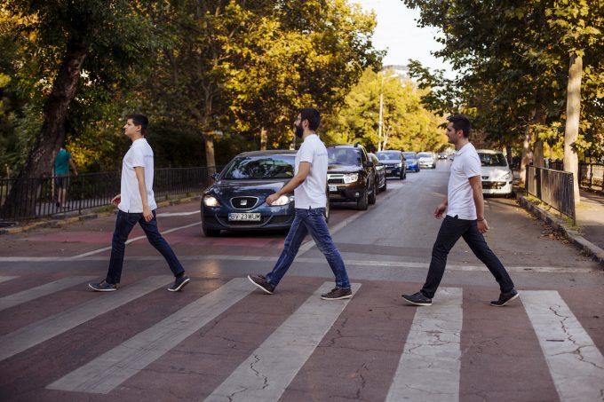 Trei bărbați trec pe trecerea de pietoni.