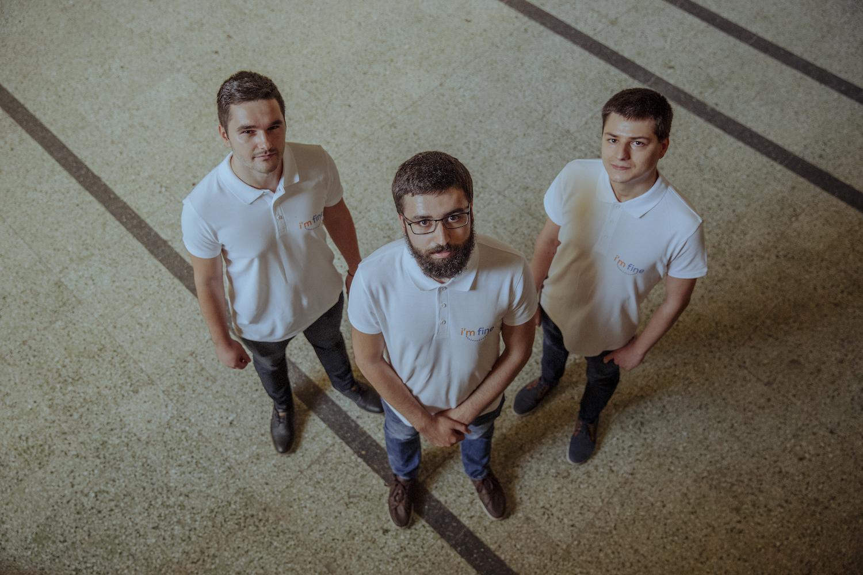 Trei bărbați în tricouri pe care scrie I m Fine privesc în cameră.
