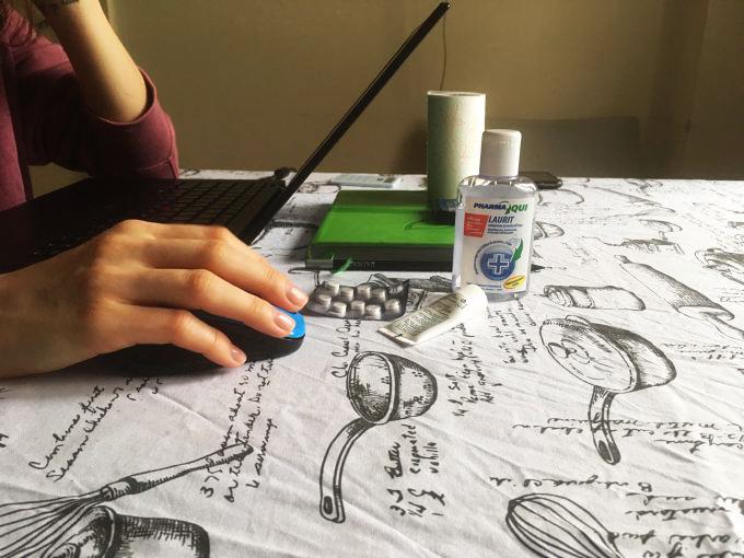 Un birou de lucru pe care există laptop, dezinfectant de mâini și pastile.