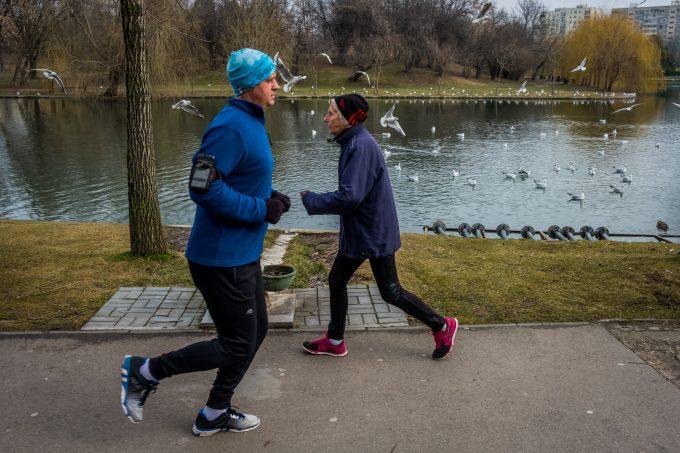 Pagu în parc, mergând în marș. Un bărbat îmbrăcat în haine sport aleargă pe lângă ea.