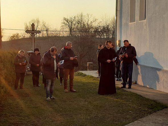 enoriașii care se roagă în curtea bisericii, alături de preot.