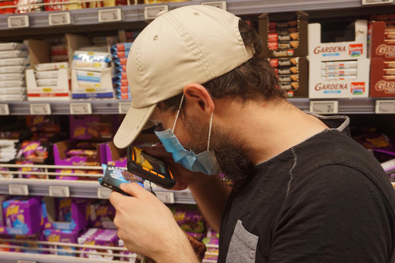Bogdan verifică eticheta unui produs în hipermarket.