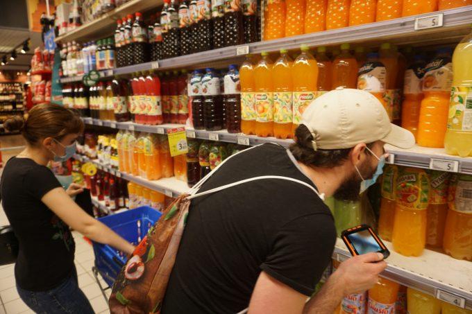 Fotografie cu Bogdan și Georgiana în hipermarket, la rafturile cu sucuri. Bogdan verifică etichetele. În mână are o lupă electronică. Georgiana are în față căruciorul pentru cumpărături.