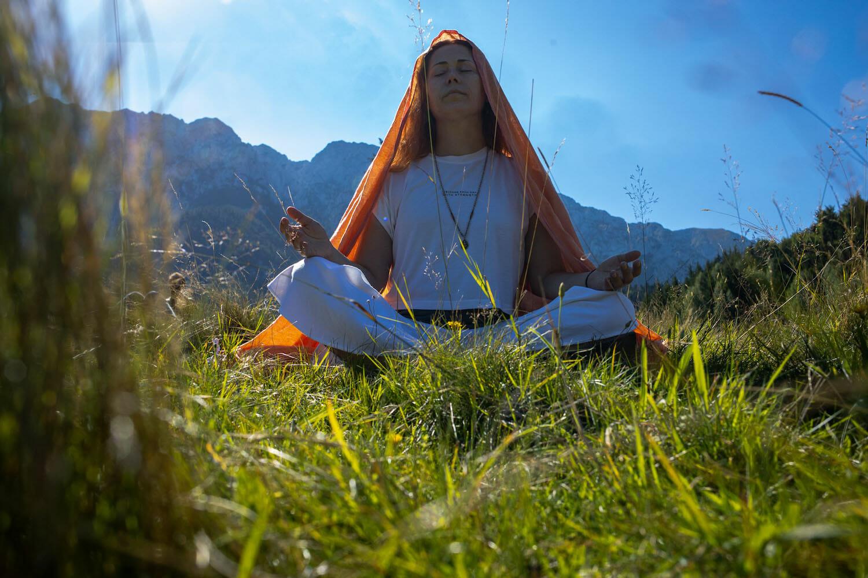 femeie care meditează în natură